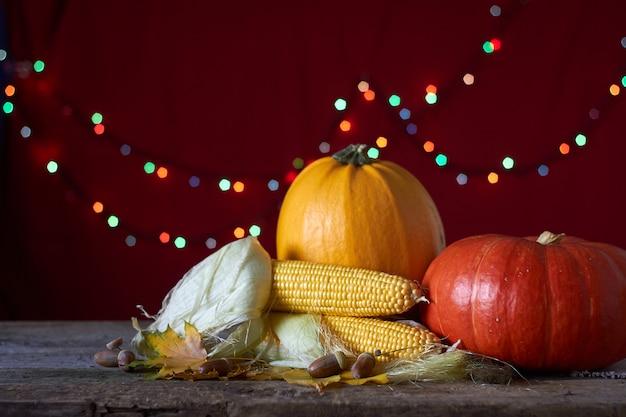 Sfondo autunnale su una superficie di legno scuro, zucche, mais, foglie appassite, ghiande e castagne