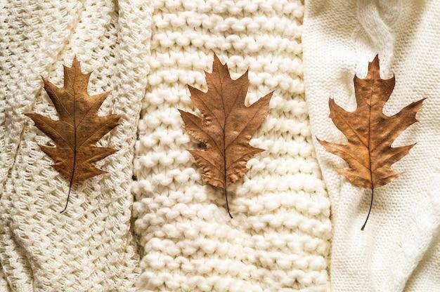 Sfondo autunno con maglioni caldi. pila di vestiti a maglia con foglie di autunno, concetto di autunno inverno.