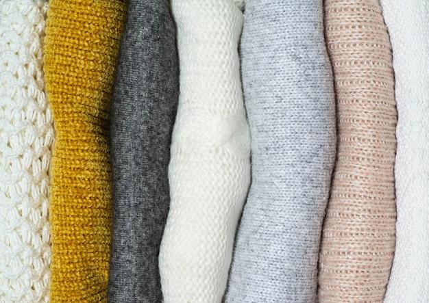 Sfondo autunno con maglioni caldi. pila di vestiti a maglia. concetto di autunno inverno.