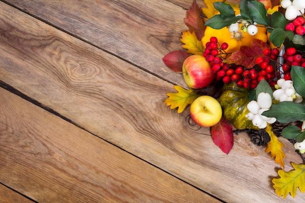 Sfondo autunno con snowberry, sorbo, mele, foglie e zucca,