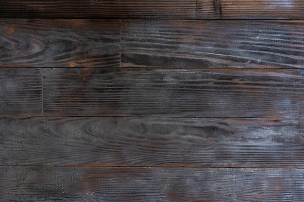 Sfondo barbecue. trama di tavola di legno bruciato. superficie di legno duro graffiato bruciato. sfondo di assi di legno di fumo. struttura in legno bruciato grunge