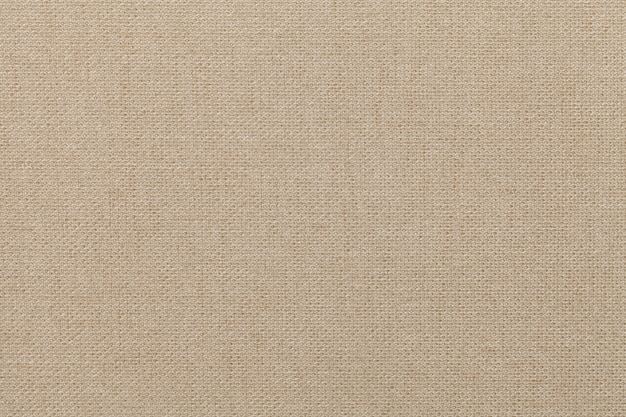 Sfondo beige chiaro da materiale tessile, tessuto con trama naturale,