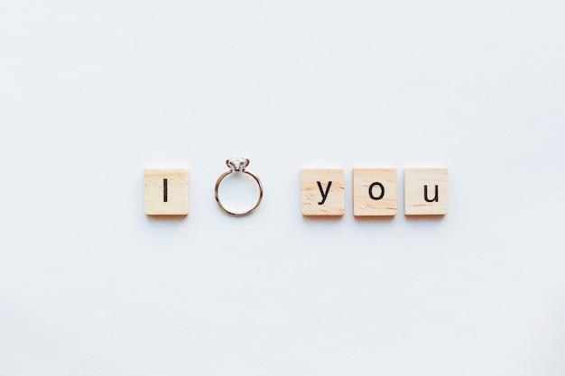 Sfondo bianco con parole in legno i love you e anello di fidanzamento con diamante.