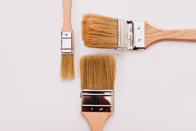 Sfondo bianco con pennelli da pittore per decorazioni e ristrutturazioni domestiche.