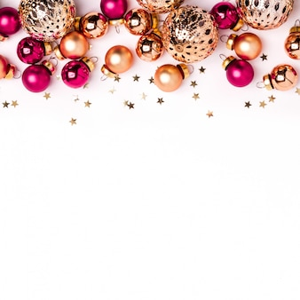 Sfondo bianco minimalista di natale. sfere d'oro e rosa brillanti e bordo dei coriandoli