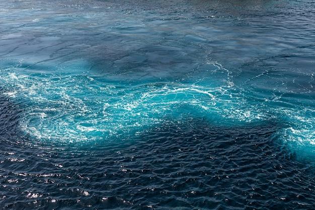 Sfondo blu del mare con onde interessanti. acqua bollente del mar mediterraneo, vista dall'alto in mare aperto. paesaggio marino blu