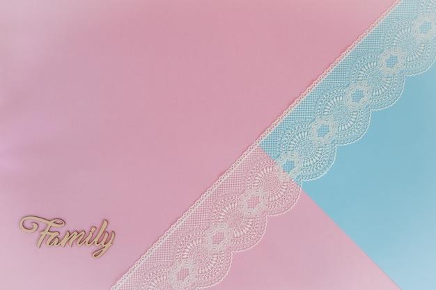 Sfondo blu rosa chiaro con pizzo e lettere di legno famiglia