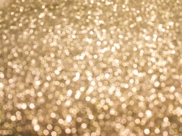 Sfondo bokeh brillante e scintillante. oro giallo - illuminazione sfocata dalla texture glitterata.