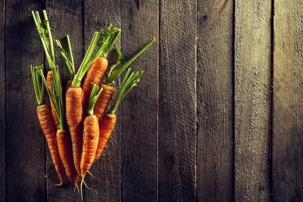 Sfondo colorato di verdure organiche di alimenti. carote fresche saporite sulla tavola di legno. vista superiore con lo spazio di copia. concetto di vita sana.
