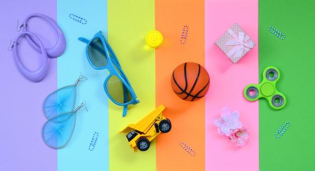 Sfondo colorato estate alla moda con orecchini, occhiali da sole, palla da basket e più elementi