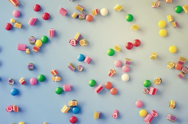 Sfondo con caramelle di cioccolato e zucchero candito multicolori sparsi.