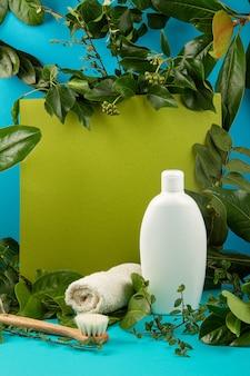 Sfondo con foglie verdi e piante e bottiglia di cosmetici. concetto di cura naturale della pelle