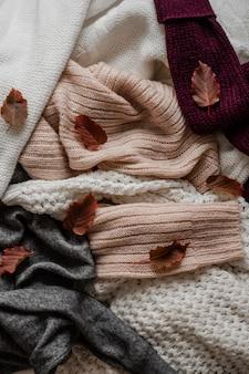 Sfondo con maglioni caldi. pila di vestiti a maglia con foglie di autunno