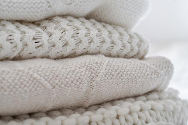 Sfondo con maglioni caldi. pila di vestiti a maglia in tonalità calde