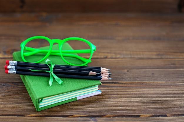 Sfondo con matite e occhiali e un libro.
