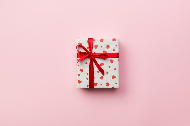 Sfondo con scatola regalo e cuori su sfondo rosa. vista dall'alto con lo spazio della copia per il testo