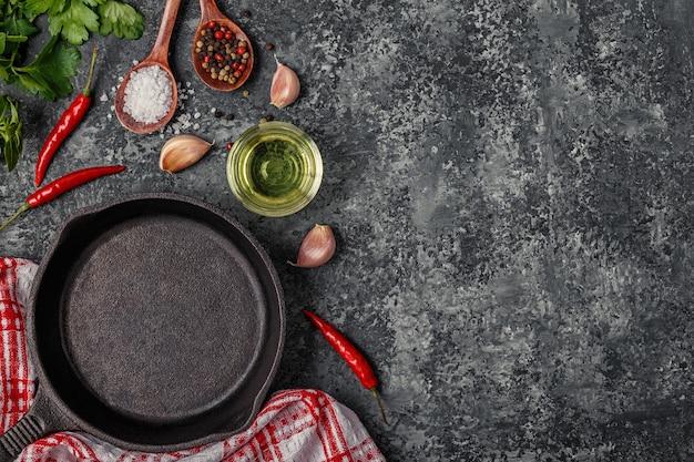 Sfondo con spezie, erbe aromatiche, olio d'oliva e padella per cucinare.