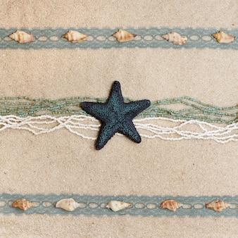 Sfondo con una stella marina blu, conchiglie, nastri e perline