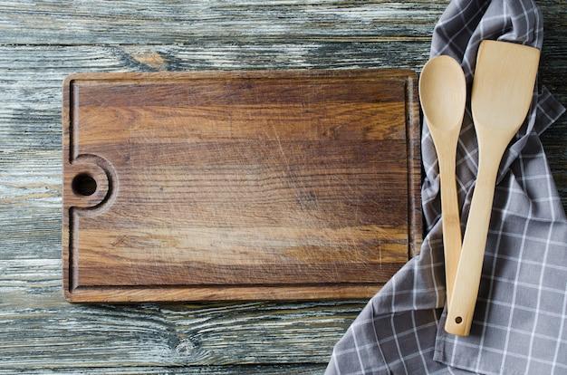 Sfondo culinario con utensili da cucina rustici sul tavolo in legno d'epoca.