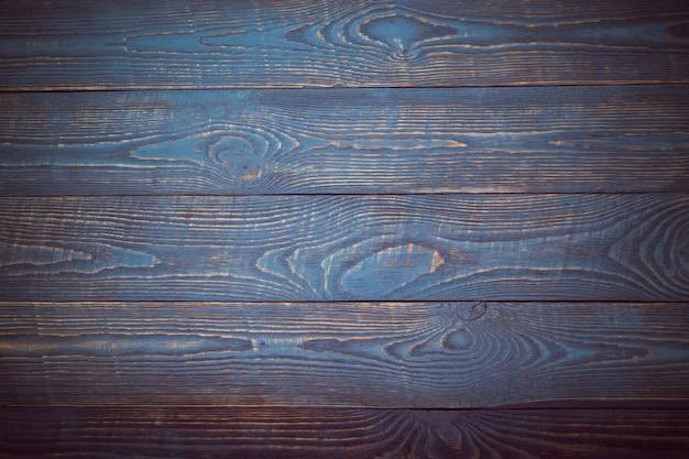 Sfondo da tavole in legno con resti di vernice blu e viola. la vignettatura