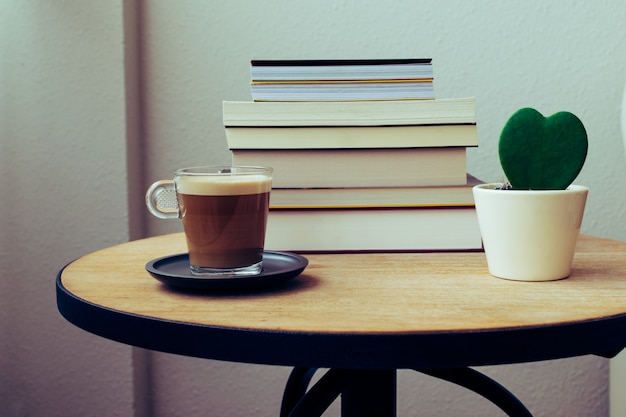 Sfondo del giorno del libro del mondo. mucchio di libri, pianta del cuore di cactus e una tazza di caffè su un tavolo di legno rotondo