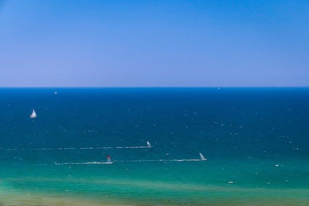 Sfondo del mare con piccole barche e yacht a vela, pratica del windsurf