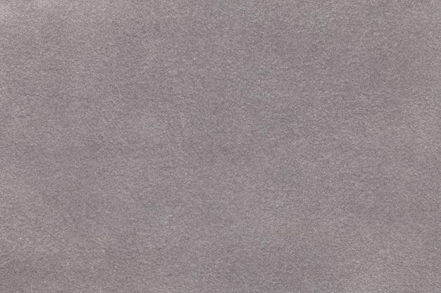 Sfondo del primo piano del tessuto in pelle scamosciata grigio chiaro. trama velluto opaco in tessuto nabuk argento
