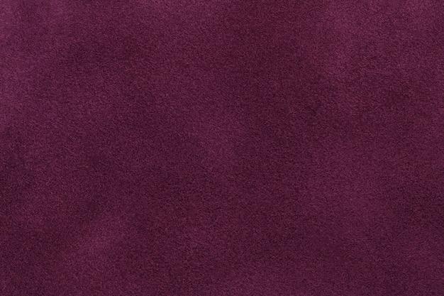 Sfondo del primo piano di tessuto scamosciato viola scuro. trama velluto opaco di tessuto nubuck vino