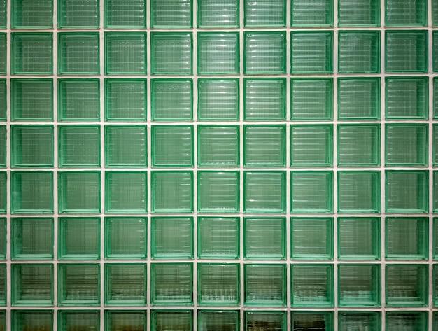 Sfondo della parete di vetro verde. parete di blocchi di vetro piastrellati lucidi in verde.