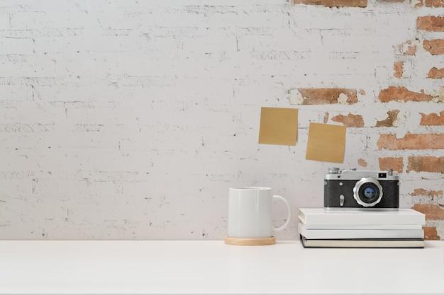 Sfondo di area di lavoro con macchina fotografica d'epoca, film, libri e copia spazio