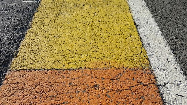 Sfondo di asfalto con linee bianche e gialle.