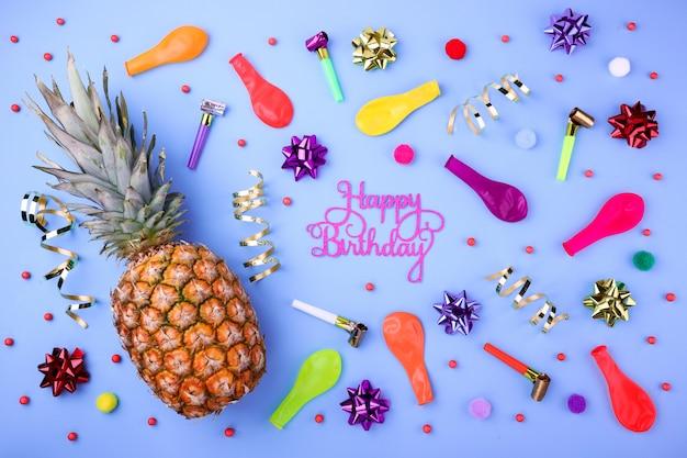 Sfondo di buon compleanno con ananas, coriandoli di festa, palloncini, stelle filanti e decorazione
