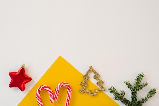 Sfondo di carta multicolore con canna di menta, ramo di abete, albero di natale creativo oro, vista dall'alto. concetto di cartolina di natale. copia spazio