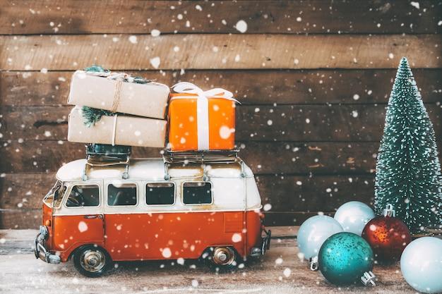 Sfondo di cartolina di buon natale vintage auto d'epoca in miniatura che trasportano regali (confezione regalo) sul tetto e albero di natale in inverno nevoso.