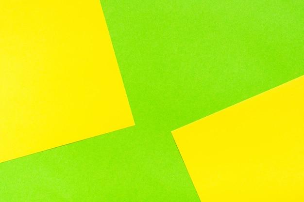 Sfondo di cartone astratto verde giallo bicolore. fogli di cartone sono impilati uno sopra l'altro.