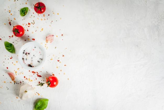 Sfondo di cibo. ingredienti, verdure e spezie per cucinare il pranzo, il pranzo. foglie di basilico fresco, pomodori, aglio, cipolle, sale, pepe. su un tavolo di pietra bianca. vista dall'alto di copyspace