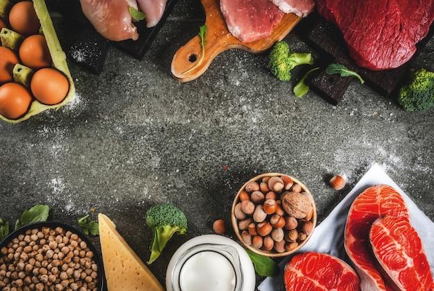 Sfondo di cibo sano. selezione di fonti proteiche: carne di manzo e maiale, filetto di pollo, pesce salmone, uova, fagioli, noci, latte. copyspace vista dall'alto, cornice di sfondo scuro