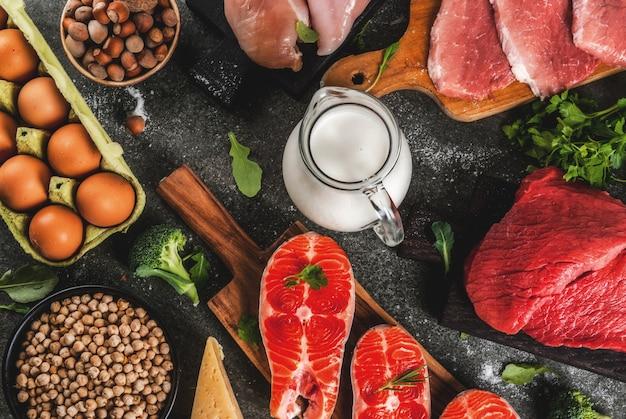 Sfondo di cibo sano. selezione di fonti proteiche: carne di manzo e maiale, filetto di pollo, pesce salmone, uova, fagioli, noci, latte. vista dall'alto copyspace, sfondo scuro