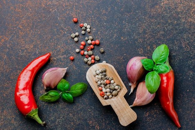 Sfondo di cibo. selezione di erbe aromatiche. pepe rosso, aglio, foglie di basilico, pepe in grani