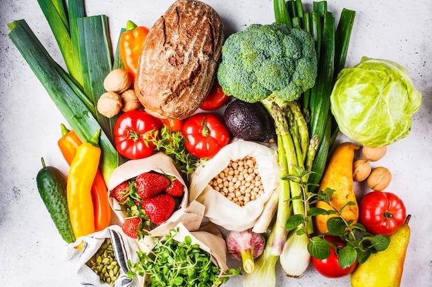 Sfondo di cibo vegetariano equilibrato verdure, frutta, bacche, noci, germogli, semi, ceci