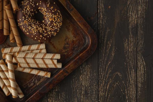 Sfondo di cioccolatini. limone, noci, biscotti e assortimento di cioccolatini pregiati in cioccolato fondente e al latte su sfondo scuro.