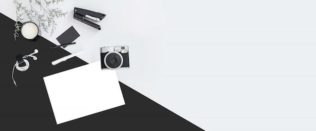 Sfondo di colore bianco e nero con rami di fiori, una tazza, auricolare, penna, spillatrice, macchina fotografica, carta di nome.
