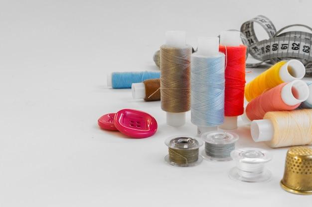 Sfondo di colore pastello, sarta e scrivania di design, accessori artigianali, rotoli di filo, forbici