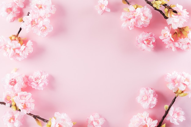 Sfondo di colori rosa pastello con motivi floreali di fiori piatti laici.