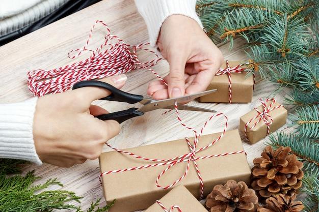 Sfondo di confezioni regalo di natale. mani femminili che imballano regalo di natale con il nastro rosso, vista superiore. vacanze invernali, pianeggianti. donna che tiene un regalo di natale ad un nastro rosso
