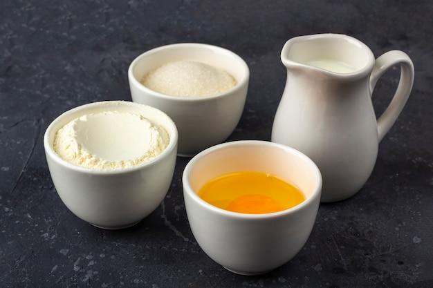 Sfondo di cottura. ingredienti per cucinare la torta (farina, uova, zucchero, latte) in ciotole sul tavolo scuro. concetto di cibo. avvicinamento/