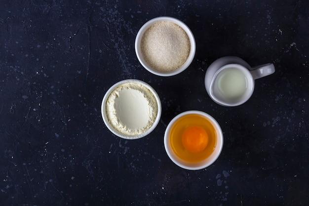 Sfondo di cottura. ingredienti per cucinare la torta (farina, uova, zucchero, latte) in ciotole sul tavolo scuro. concetto di cibo. vista dall'alto, layout piatto, copia spazio per il testo.