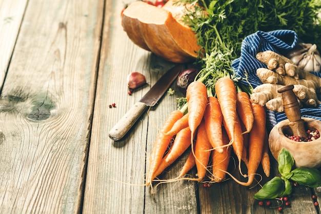 Sfondo di cucina cibo sano. carote fresche del giardino, cipolle, zucche, zenzero e spezie su legno rustico