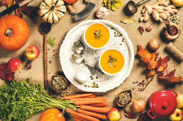 Sfondo di cucina cibo sano. ingredienti vegetali e zuppa fatta in casa. carote fresche del giardino, cipolle, zucche, zenzero e spezie su legno rustico, vista dall'alto, copia dello spazio