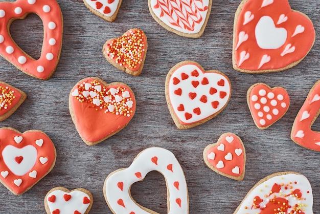 Sfondo di decorato con glassa e biscotti a forma di cuore smaltato su grigio, piatto laici